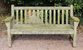 an old teak garden bench with flat arms and slatted back seat