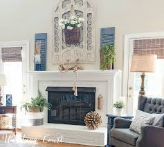 farmhouse style painted brick fireplace decorated with simple and organic elements for the summer