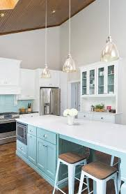tiffany blue kitchen features a vaulted ceiling framing skylights accented with a three mercury glass dome pendants illuminating a tiffany blue island
