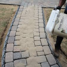 pouring polymeric sand over the pavers
