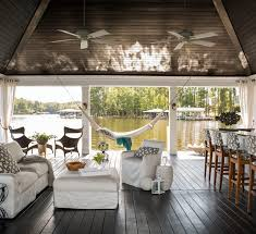 boat dock transformed into lounge features vaulted paneled ceiling dotted with ceiling fans over white slipcovered sofa and white slipcovered chair accented