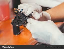 художник татуировки в белые резиновые перчатки готовится сделать