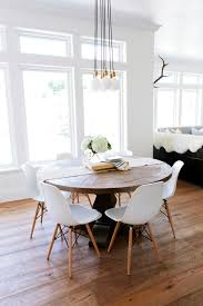 A Rustic Round Wood Table Surrounded By White Eames Dining Chairs