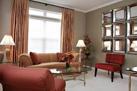 living room red and brown sofa having cushions with oval glass table on white rug