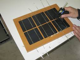 gluing the solar cells to the wooden backing