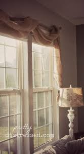 Love this simple burlap window treatment/ stick looking rod set up. pair  with cream curtains and big burlap bow tiebacks.