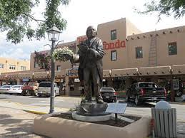 taos plaza and la fonda hotel with sculpture of padre jose antonio martinez in the foreground