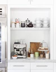 Beautiful kitchen nook next to glass-front refrigerator is filled with a  coffee station boasting an espresso machine under a shelf filled with a  French ...
