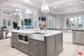 the kitchen features a large center island and bright ceiling lights along with smooth white countertops