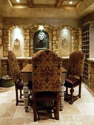 A neutral toned Tuscan wine cellar has tile floors and a table and ...