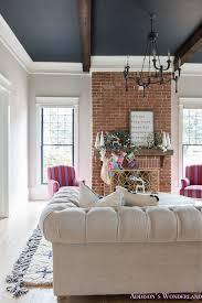 vintage living room black ceiling brick fireplace dark wood beams anthropologie home tufted sofa 3 of 23