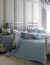 a grey bedroom with a silver finish bed a mirror nightstand and blue and grey
