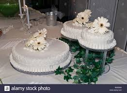 Three White Wedding Cakes With White Floral Decoration And Greenery