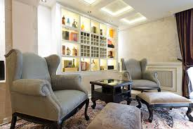 this room makes elegant decorating look easy the side table is perfectly positioned between two vintage arm chairs each with their own foot stools