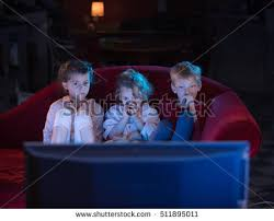 kids watching tv at night. at home by night, three scared kids watching tv night l