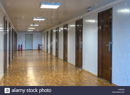 office hallway. Long Office Hallway With Many Doors Of Dark Red Wood. - Stock Image W