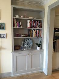 Here's how this part of the room could look, with built-in cupboards below  the shelves, cornicing and the fireplace painted white. A central chande