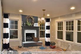 dinin room with a dark gray fireplace and black and white striped dries