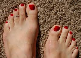 male painted toes in red nail polish