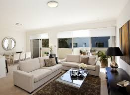 cozy living room with white couches and brown rug