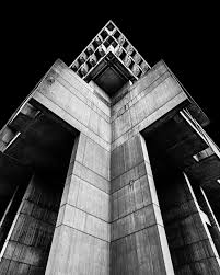 Taken from the perspective of ground level, a medium-sized concrete  building shadows over