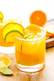 orange margarita in a gl with lime and orange slices