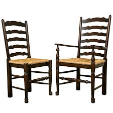 set of eight english oak wavy ladder back chairs with rush seats for