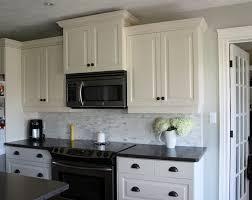 white kitchen cabinets with dark granite countertops