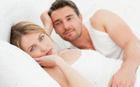 Lovely Couple In Bed Lying In Bedroom Lovely Couple Lying Down Together In Their Bed At Home Stock Photo