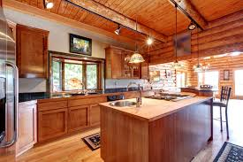 log cabin kitchen with butcher block island and track lighting