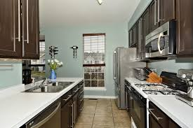 contemporary kitchens with dark cabinets. A Contemporary Kitchen With White Countertops, Gray Walls, And Dark Cabinetry. The Galley Kitchens Cabinets
