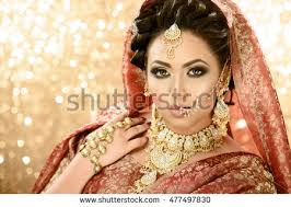 pretty in traditional indian stani bridal costume with heavy makeup and jewellery against a glittery