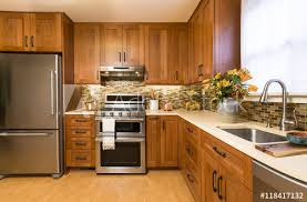 contemporary upscale home kitchen interior with cherry wood cabinets quartz countertops sustainable recycled linoleum floors stainless steel appliances