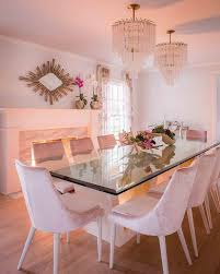 modern dining table with a glass top and beveled edges feature a white geometric base surrounding pink velvet chairs on blond hardwood floors