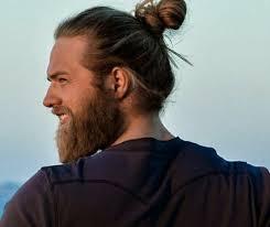 a hipster with a gy beard and a full man bun hair style