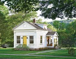 Cottage Design Ideas a small white cottage with yellow door surrounded by trees