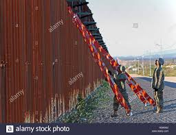 Pfc. Ryan Lopez and Spc. Dustin Carpenter, 87th Sapper Company, position  their ladders to install concertina wire on a border wall near the city of  Douglas, Arizona on Nov. 12, 2018. U.S.