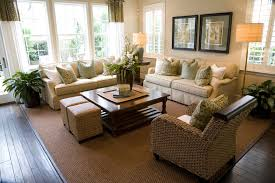 Contemporary living room design with two matching off-white sofas loaded  with white and soft