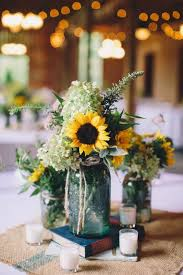 Rustic sunflower centerpiece with burlap, candles and mason jars
