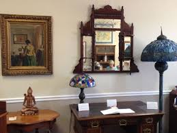 antique tiffany floor lamps near small vintage wooden table also small mosaic table lamp under wooden framed mirror plus small painting