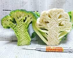 a broccoli and a cauliflower carved with a em sayagata em