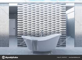 bathroom interior with two long mirrors a curved white bathtub standing near a brick pattern wall a towel is hanging on the tub