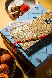 rakhi gifts diya in a puja thali indian currency notes envelope and sweet