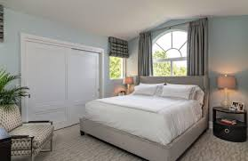 big walk in closet bed pillows chair bedside tables lamps windows curtains decorative plant contemporary bedroom