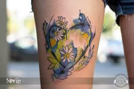 сердце с цветами в стиле акварель на бедре фото татуировок