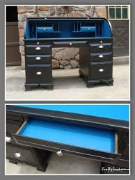 the black roll top desk has plenty of storage and a bright blue pop of color