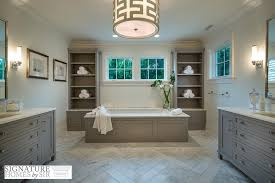 gray wainscoted bathtub flanked by tall gray built in shelves