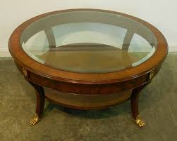 small round mahogany coffee table with glass top brass