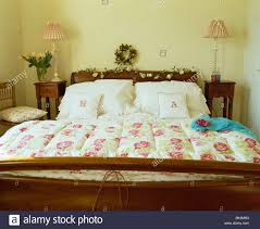 Rose-patterned quilt and white pillows on mahogany bed in country ... & Rose-patterned quilt and white pillows on mahogany bed in country bedroom  with lamps on small tables on either side of bed Adamdwight.com