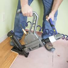 pneumatic nailer on partially intalled hardwood floor